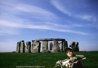 Wallpaper of Justin Bieber Riding a Bike near Stonehenge Stone Monument background