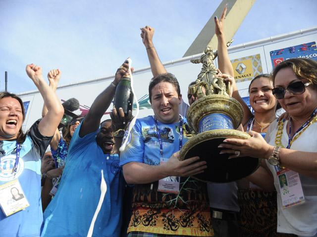 Integrantes da Vila Isabel erguem o troféu e comemoram a vitória com champagne. Foto: Tânia Rêgo/ABr