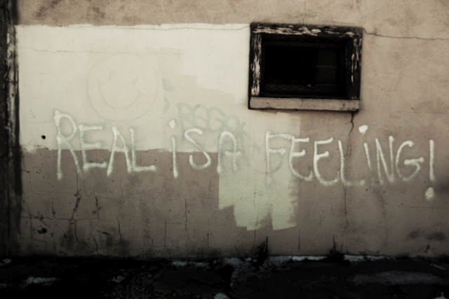"A graffiti quote in Denver that says, ""Real is A Feeling!""."