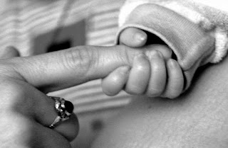 Image: newborn holding mom's finger, on MorgueFile