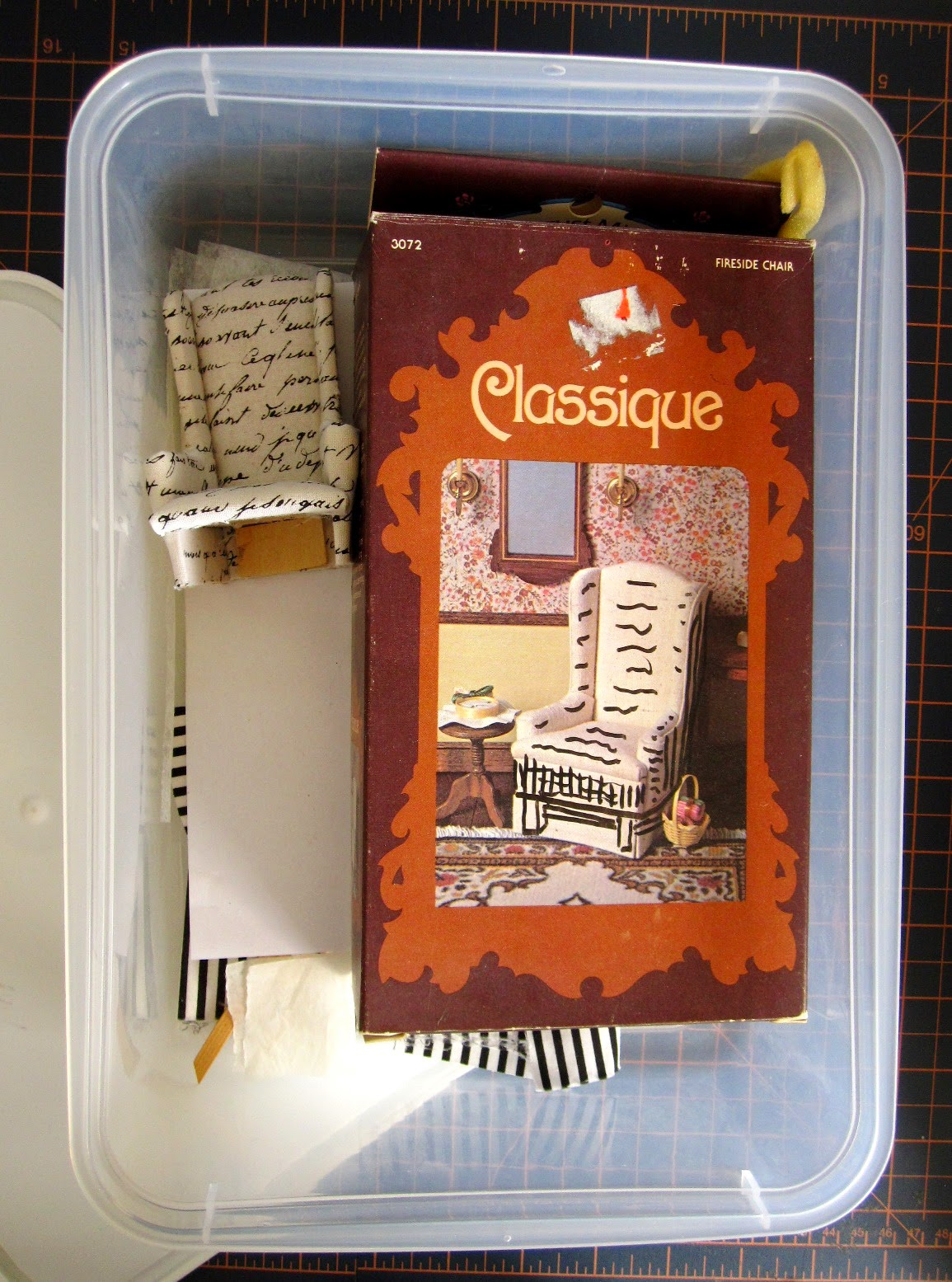 Plastic storage box containing a dolls' house miniature wing chair kit package, a half-finished chair and various pieces of fabric.