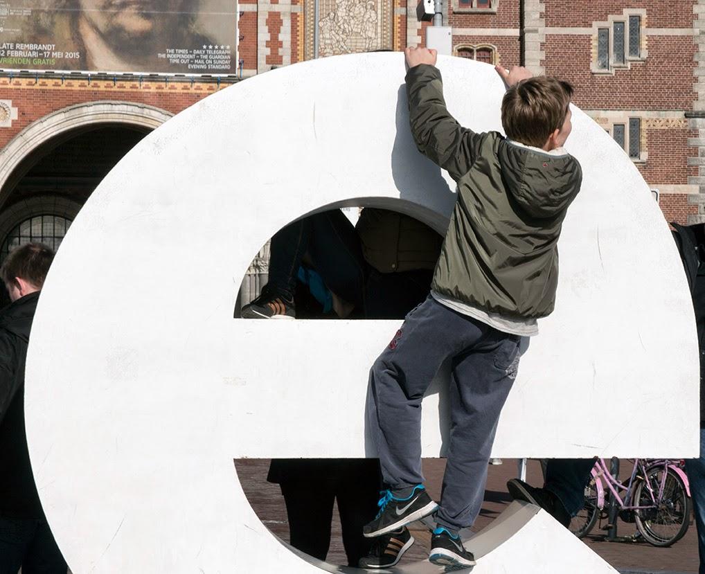 boy climbing on letter E