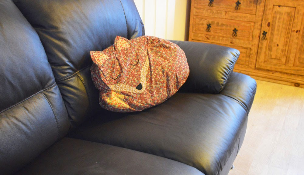 Fox cushion on leather sofa