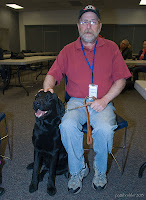 A man wearing blue jeans and a red shirt with a blue lanyard around his neck and a baseball hat is sitting in a chair with his hand on the head of a black lab. The lab is sitting to the left of the man and has its mouth open. The man is holding a brown leash in his left hand.