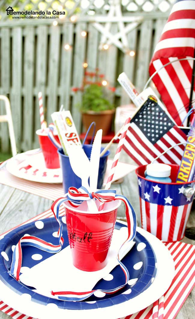 American flags, paper plates table with wire spool.