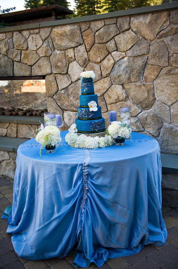 A beautiful rich blue wedding cake set over four tiers adorned with fresh