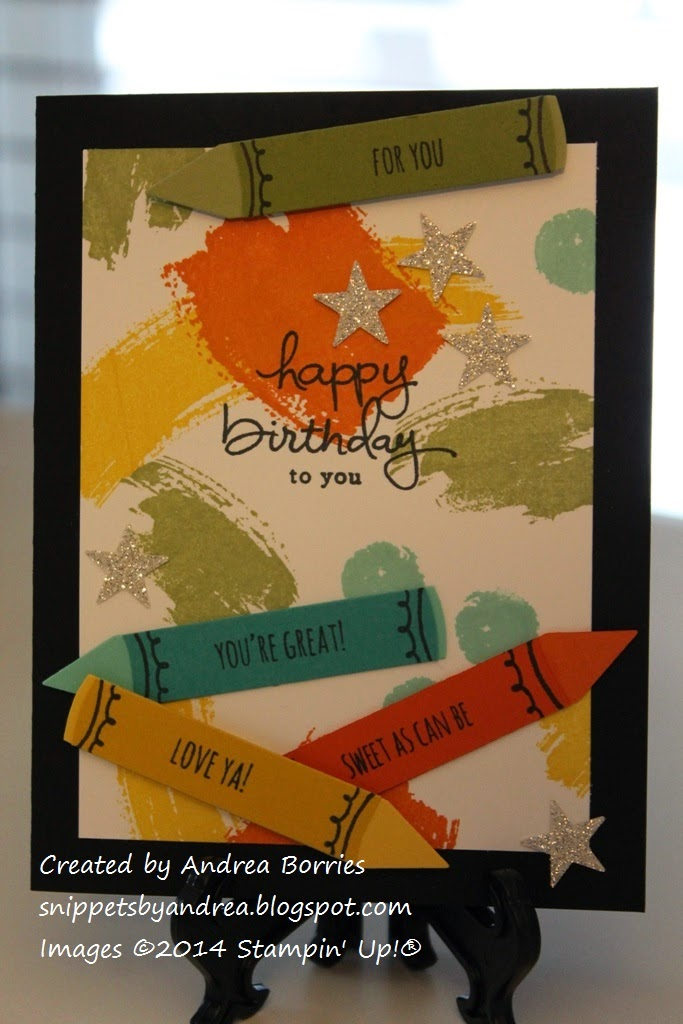 "Black card with a white layer stamped with ""swooshes"" of orange, yellow, green and blue. Die-cut crayon shapes of the same colors are stamped with different sentiments. The main sentiment is ""happy birthday to you."""