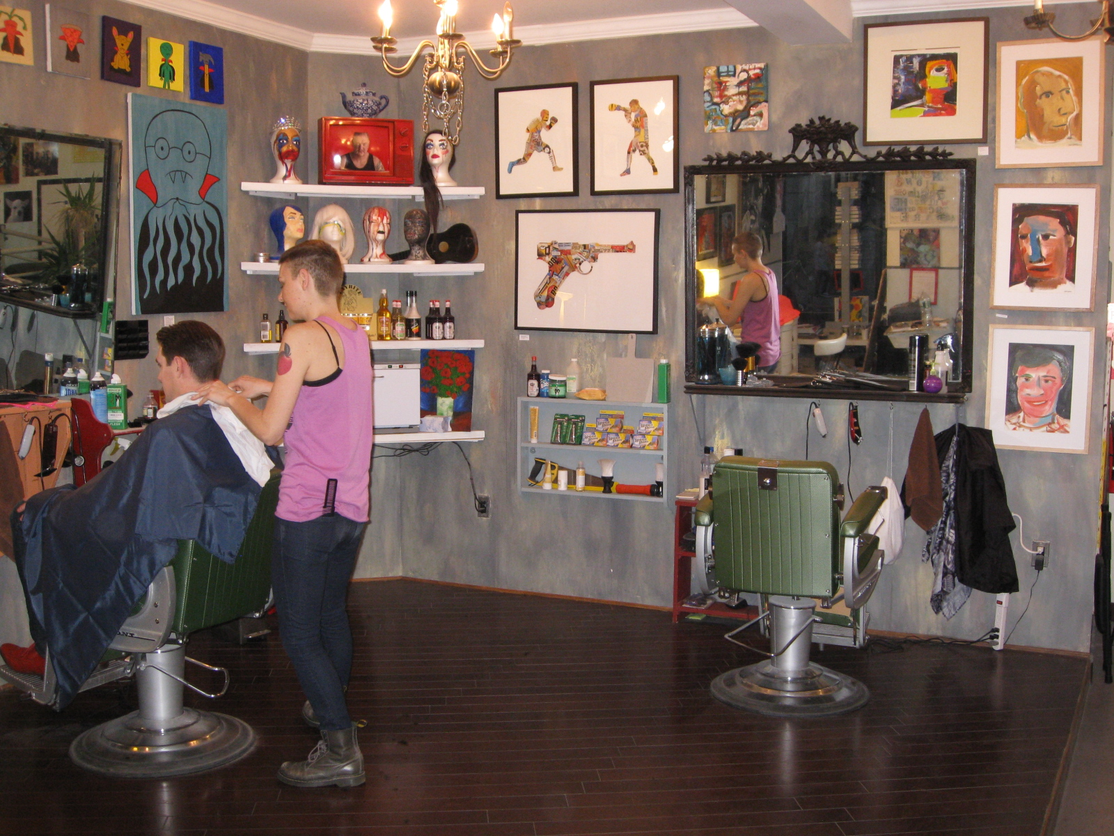 ... . Artwork from various artists adorn the walls of her barber shop