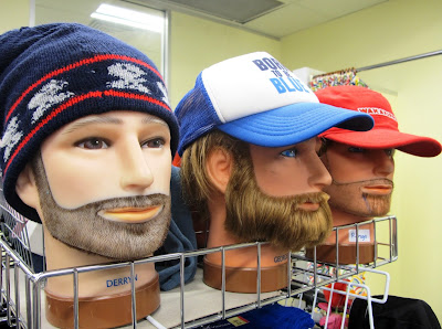 Three bearded male mannequin heads wearing hats.
