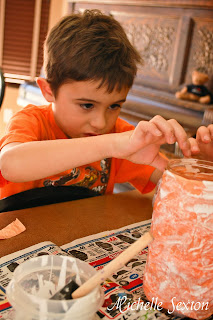 child adding eyes to a jar