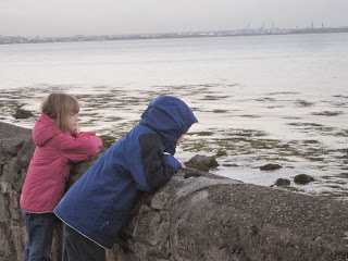 Children looking over a low wall at the sea