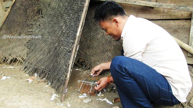 Salah satu mahasiswa sedang memasang perangkap Tikus di luar rumah