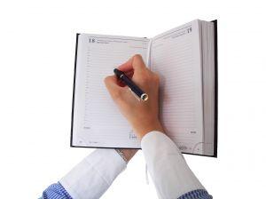 Рука, пишущая в ежедневнике