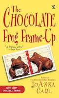 Book cover for The Chocolate Frog Frame-Up by JoAnna Carl