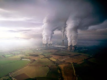 Cooling towers belch steam at the Drax power plant in North Yorkshire, England. It is at the center of the debate over whether burning wood pellets reduces harmful greenhouse gas emissions. (Credit: Jason Hawkes, courtesy of Flickr)  Click to Enlarge.