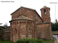 L'absis i el campanar de Sant Martí del Brull, i al fons a la dreta les restes del Castell del Brull