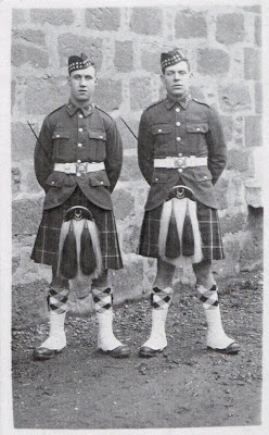 Two youngish soldiers in full highland army uniform, glengarry caps with chequered bands, khaki tunics, tartan kilts, large sporrans, long socks with chequered tops and white spats.