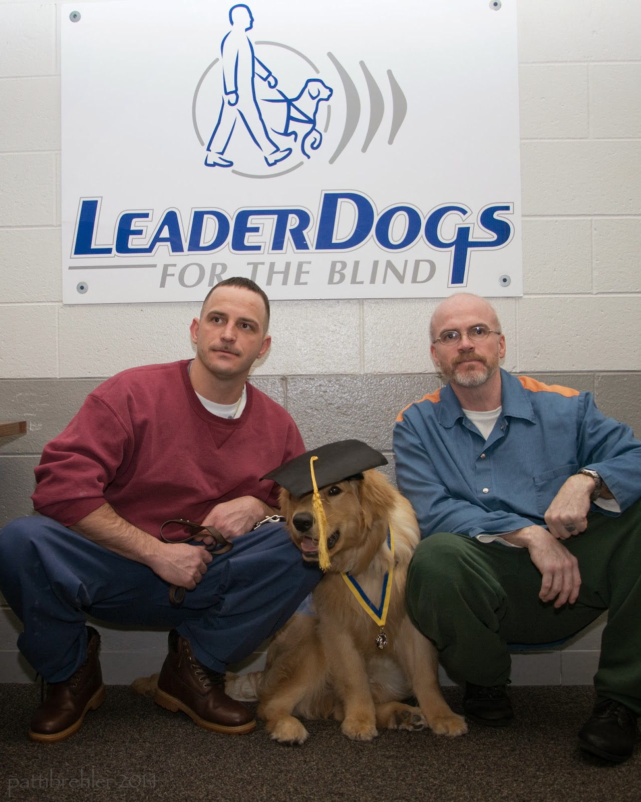 Two men are sqatting with the same golden retriever between them. The dog is sitting down and is wearing a black graduation cap and medal around its neck. The man on the left is wearing a maroon sweatshirt and blue pants. The man on the right is wearing a blue shirt and green pants. On the wall behind them is a white poster with blue letters that say Leader Dogs for the Blind, with the Leader Dogs logo above it of a person with a guide dog.