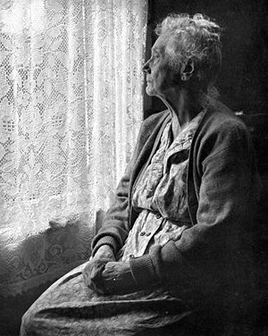 old woman looking out of window with lace curtains