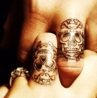 Sugary skull tattoos on fingers of a couple