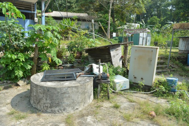 Residents told The Straits Times they drew water from wells in their backyards. One uses a motor pump to fill containers in his home.