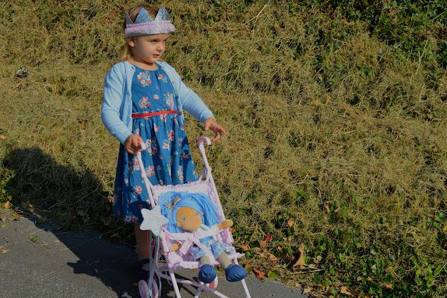 Fancy dress girl pushing doll in pushchair