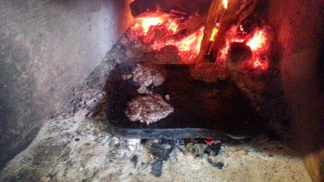An image of logs burning in a old hearth