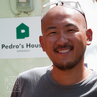 Pedro, a Korean man in front of a sign for Pedro's House in Gwangju, South Korea.