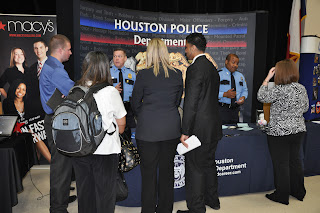 Well-dressed students gathered about a booth operated by the Houston Police Department.