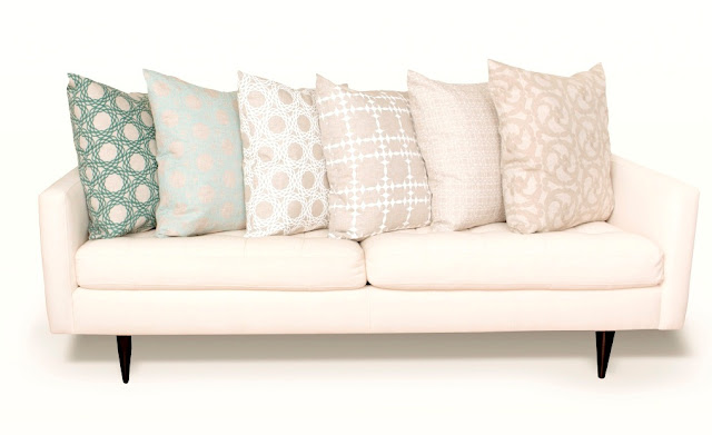 Six COCOCOZY pillows in different colors and patterns on a white sofa