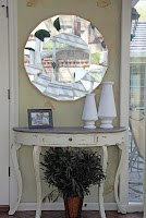 round mirror and rustic console