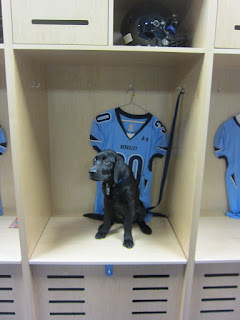 Coach is sitting in the locker room box with a #30 blue jersey behind him.  You can also see a blue helmet.