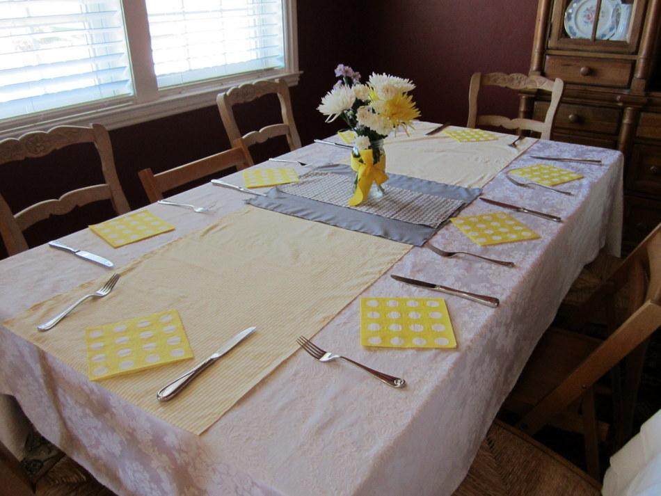 ... Table Runners, With Gray Fabric In The Center And Grey Pattered Fabric  On Top. Cheery Yellow And White Flowers In Clear Mason Jars Tied With Yellow  ...