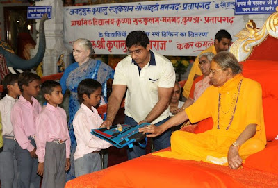 Jagadguru Kripaluji Maharaj giving school bags to boys