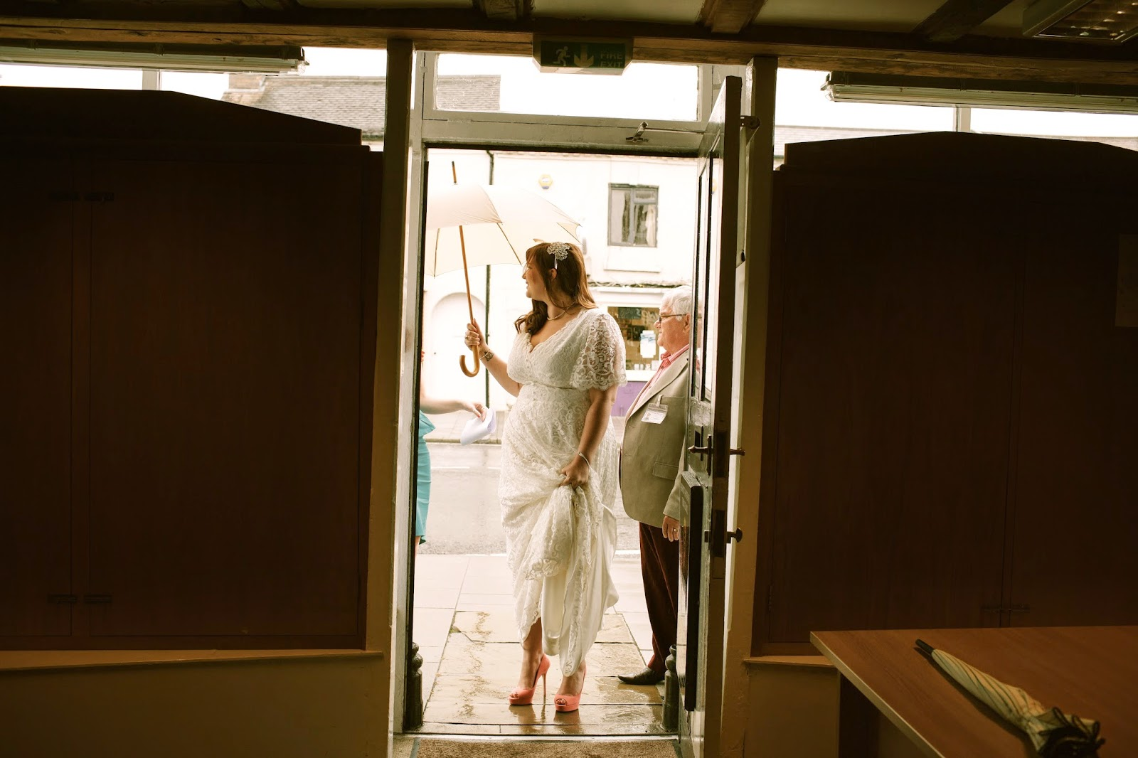 A Curvy Girl Stands in a doorway in her wedding dress