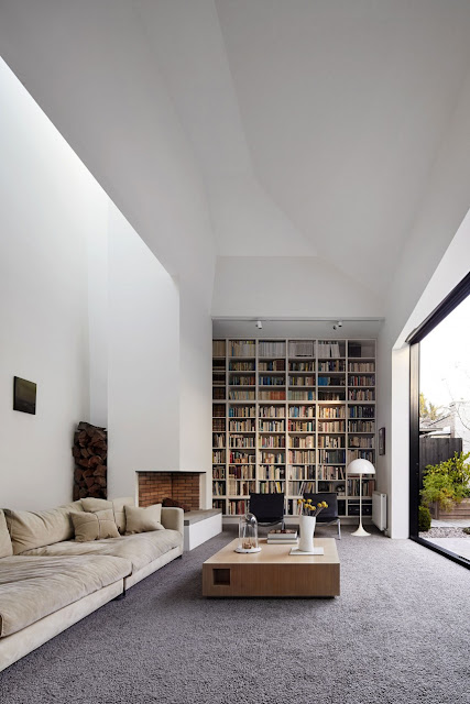 Modern reading room with high book shelf, modern fireplace.