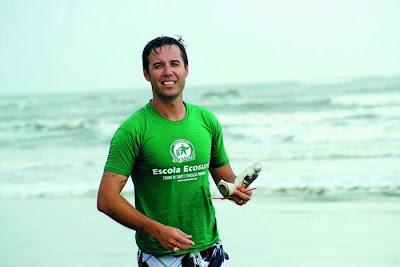 o surfista João Malavolta, fundador da Ecosurfi, retirando lixo da praia. Foto de Liana John