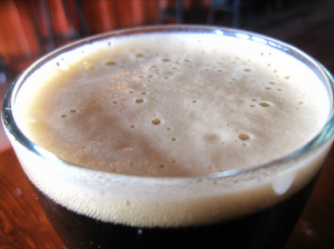 close up of head on a glass of dark beer