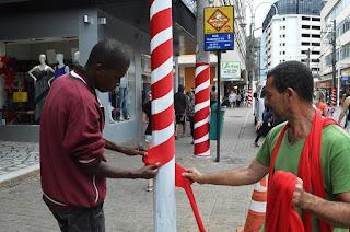 Cerca de 500 postes estão recebendo reforço na pintura, em branco, e já começaram a ser envelopados com tecido vermelho