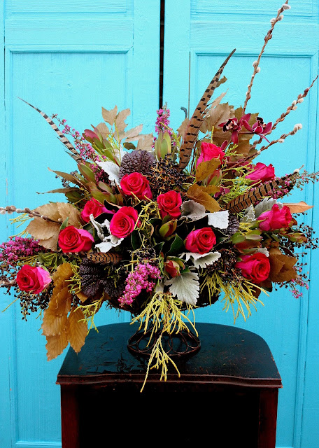 Fall Thanksgiving centerpiece with privet, chard, magnolia, and pheasant feathers.  Isha Foss Events