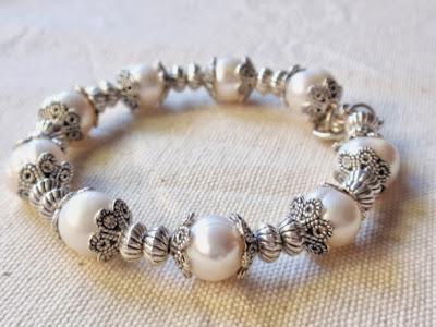 pulsera artesanal de perlas y abalorios plateados con cierre mosqueton