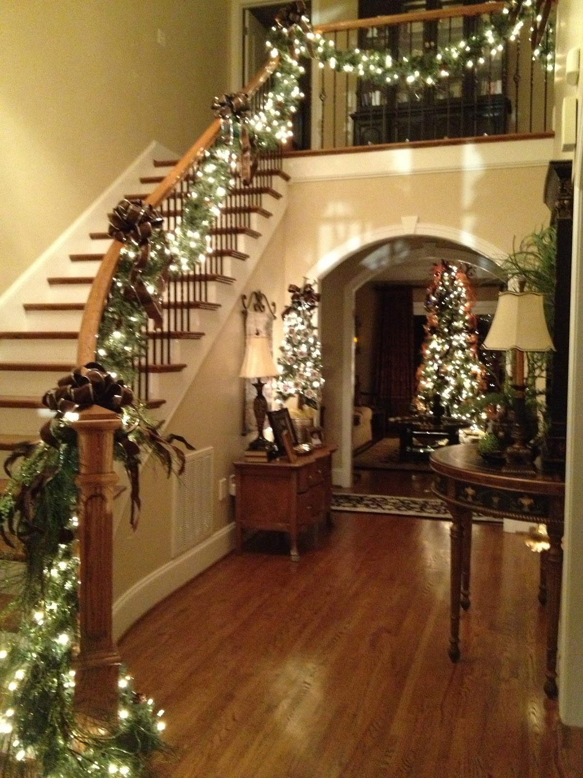 i always decorate my stairs with lighted garland because it looks great at night i add bows every few feet and at each end especially at the banister