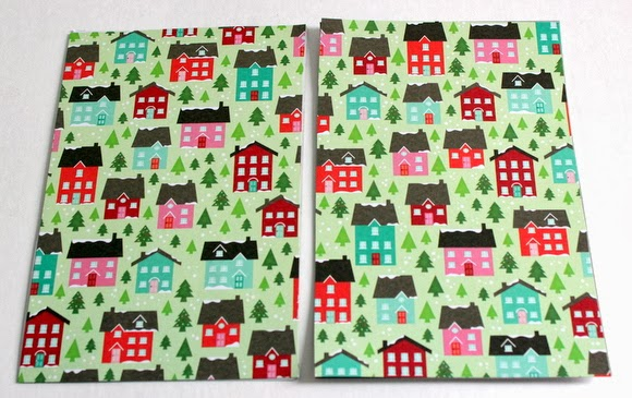 Glue the Christmas paper to your cover on the front and back sides. Isn't this wrapping paper with little fir trees and red and green houses so cute?