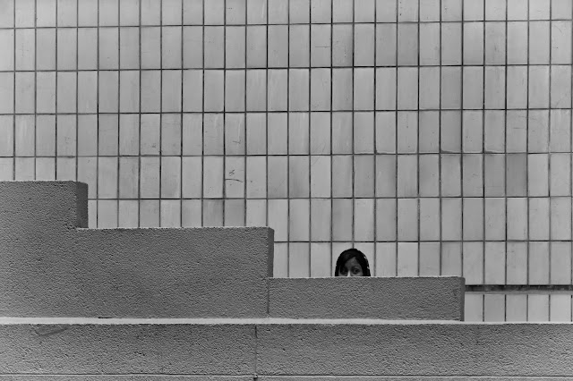 A woman peers out from behind a wall against a backdrop of rectangular tiles in this street photograph from Cape Town South Africa
