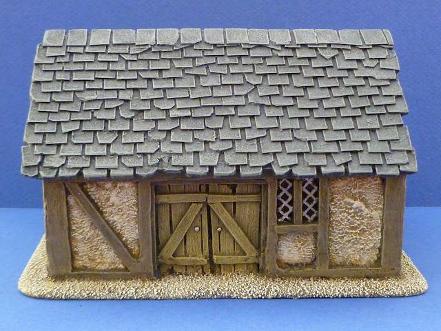 La version personnalisée: les ardoises ont remplacé les tuiles. La toiture et les boiseries ont été légèrement endommagées afin de montrer une grange ayant vécu. Le crépi a été repeint lui aussi. La bâtisse a été collée sur un socle en bois fin.