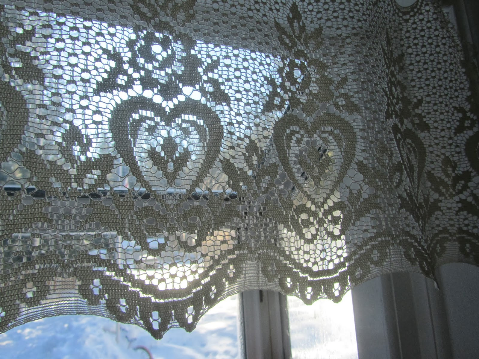 sun streaming through heart patterned lace curtains