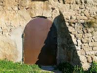 Detall del portal d'entrada d'arc de mig punt adovellat i del massís contrafort