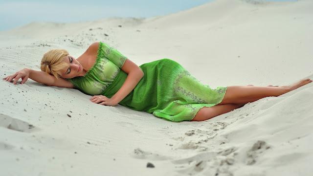 Foto van een vrouw in groene jurk liggend op het strand