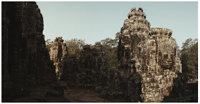 lone tourist walking inside bayon temple, cambodia
