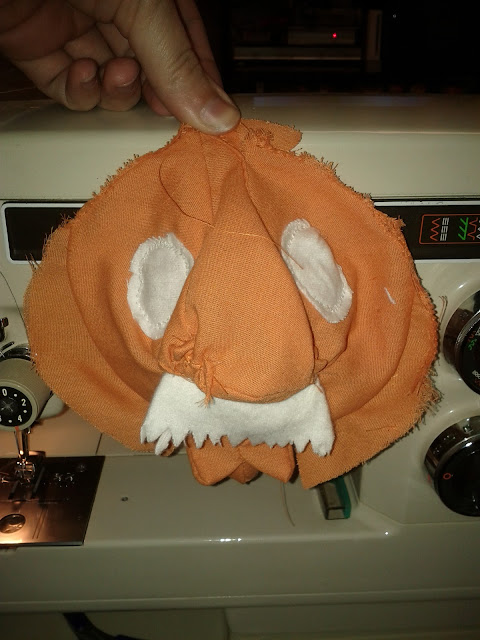 The orange ball is now sewn together and white eyes and a white mustache have been added to give the star a face.